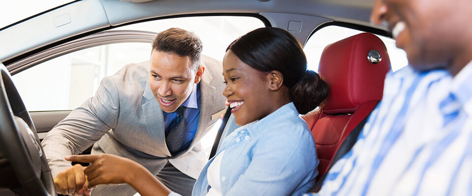 Salesman showing new car to couple